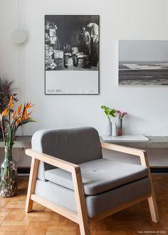 Sala de estar tem poltrona com desenho contemporâneo, quadros em  branco e preto e banco de concreto.