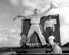 Landing Signal Officer Ensign R. J. Grant guiding in a F6F Hellcat fighter aboard USS Enterprise, 13 Mar 1945