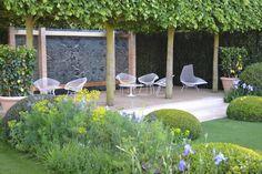 jardin contemporain, parement mural en pierre façon marbre, gazon, buis boules et meubles design