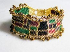 """Beadwoven with tiny Japanese Delica beads, this colorful cuff bracelet will look great with any outfit. Bracelet edge is trimmed with bronze colored fresh water pearls. Closes with a gold plated box clasp. Bracelet is around 7"""" long."""