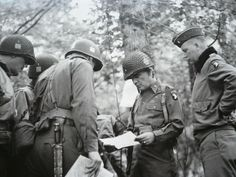 US Paratrooper photo taken at Bastogne of General McAuliffe's (right center) Staff in a field meeting.