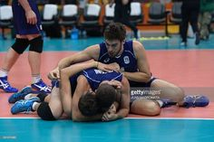 Italy's Luca Vettori (up) and teammates lie on the court as they celebrate after winning their men's semi-final volleyball match against USA at Maracanazinho Stadium in Rio de Janeiro on August 19, 2016, at the Rio 2016 Olympic Games. / AFP / Juan Mabromata