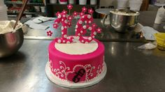 A Sweet 16 fondant covered cake with plaque and flowers on curling wire.