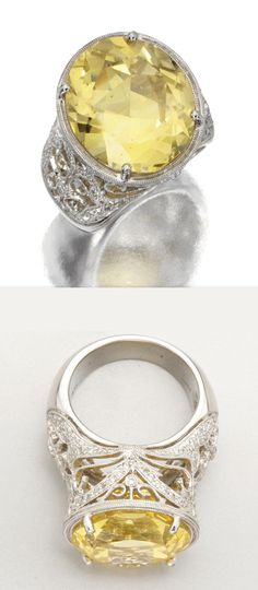 YELLOW SAPPHIRE AND DIAMOND RING - set with an oval sapphire weighing 27.95 carats, within an openwork gallery set with numerous small round diamonds weighing approximately 1.00 carat, mounted in platinum