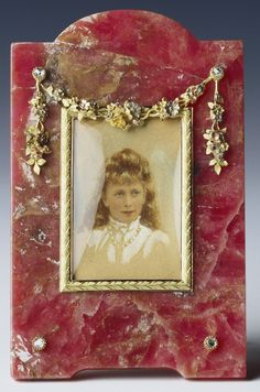 Fabergé rhodonite frame with four-colour gold, silver-gilt, rose diamonds, mother-of-pearl. The frame contains a watercolour portrait miniature of Princess Mary, The Princess Royal, the only daughter of King George V and Queen Mary who married Viscount Lascelles (later the 6th Earl of Harewood) in 1922. The portrait miniature was painted in about 1906 and the frame was purchased by the Prince of Wales (later King George V) from the London branch in December 1909 at a cost of £14 15s.