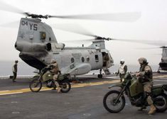 Marines from the 26th Marine Expeditionary Unit prepare to load their M1030 motorcycles into a CH-46E Sea Knight helicopter on the flight deck of the amphibious assault ship USS Kearsarge (LHD 3) during flight operations in the Mediterranean Sea on 18 April 2005