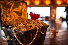 A simple center piece composed of a mini treasure chest and fake gold coins and jewelry