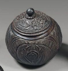 NOIX DE COCO formant pot à tabac sculptée d'armoiries, pipes, fleurs et feuillages. Première moitié du XIXe siècle