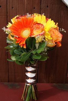 What a great bouquet for a fall rustic wedding!  Made of limonium, large orange and yellow gerberas, import roses and pittosporum greenery