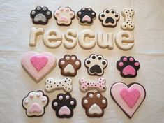 Dog decorated sugar cookies for humans. Royal icing. Brown, chocolate, pink, white. Dog paw, dog bone, Helvetica letters. Sparkling sugar. PugHearts Pug Rescue of Houston.