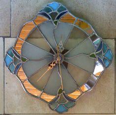 reloj realizado con perfil de plomo. Vidrios azules y celestes para las flores. Espejos para los arcos entre ellas y vidrios stipolite y arenado para los gajos centrales