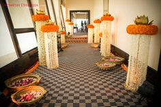 Love this entrance pathway adorned with hanging white flower elements with marigold top finished with Lotus Centrepieces and floral rangoli on the floor
