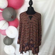 Edgy and trendy tunic. Perfect color for fall, but you can carry this into winter and spring. Printed orange/navy double pleat neck with gold tone button closure. Looks great with a pair of navy Leggi