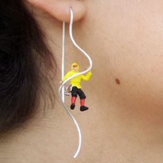 Product and jewellery designer Rita Botelho has created a series of earrings featuring tiny figurines, including this one in rock-climbing gear.