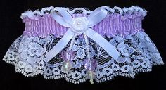 Be the Envy of everyone with this Garter in LT ORCHID satin band and matching double hearts all on white lace. The white satin bow has a mini rose with a pearl eye in the center. Lt Orchid Garter for Wedding Bridal Prom Fashion. Style # FM-2AN-430 / Visit: www.garters.com/page13a.htm