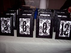 DIY Table Numbers...spray paint dollar store frame, pick a scrapbook paper and spraypaint a wooden number OR could print it on the scrapbook paper.