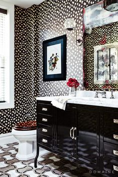 Patterned black and white wallpaper and patterned tile marble floors are paired with a marble and black vanity with red accents for a very elegant look.