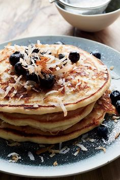 This quick and easy 35-minute coconut pancake recipe incorporates shredded coconut, buttermilk, honey, powdered sugar, blueberries and maple syrup to create the ultimate breakfast recipe. Whether you're looking to eat this coconut recipe on its own or alongside eggs, bacon or sausage, it's a great choice for a brunch recipe.#breakfastrecipes #brunchrecipes #pancakerecipes #coconutpancakes #weekdaybreakfasts