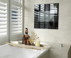 A plank tray and a few sprigs in a jar warm up a sleek bath, complete with a flush-mounted plasma TV.