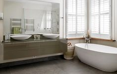 Large and modern double en-suite bathroom design. Freestanding bath tub, floating bathroom cabinets and couples' sink area.