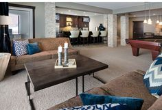 Morrison Homes Savannah Showhome - Winner of a 2013 #SAMCalgary Award, rich brown sofas with printed pillows, a wood grain coffee table and great accessories bring life to this great living room done by Shelly Curran and Kaitlyn Harris.