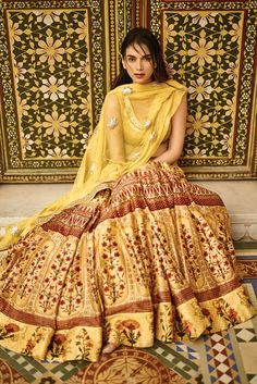 A stunning floral, chanderi silk, digital printed lehenga with a canary-yellow, raw silk choli and a gota patti detailed net dupatta.INR 100,000.00