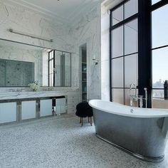 Waterworks Candide Freestanding Oval Cast Iron Tub Placed in Front of Floor to Ceiling Windows