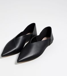 Flat black leather shoes. Foldable heel. Pointed toe. Heel height of 0.6 cm