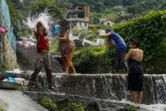 Nepalese women and young boy splash water on each other as they wash in a small waterfall in Naryanthan village on the outskirts of Kathmandu, Nepal, August 17. (NARENDRA SHRESTHA/EPA)