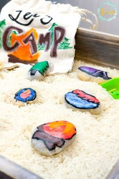 This camping sensory bin uses a base of dry white rice and camping story stones for fun sensory play for kids. Great before a family camping trip. #sensoryplayforkids #sensorybin #viewsfromastepstool #sensorybins #kidsactivities #preschool #campingactivitiesforkids