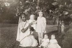 Ayah with children. An Indian ayah (nursemaid) poses beside her British charges, a young girl and a baby, in the garden of a colonial residence. Two toy dolls are propped up for the camera in the foreground. Calcutta (Kolkata), India, October 1932. Kolkata, West Bengal, India, Southern Asia, Asia.  - stock photo