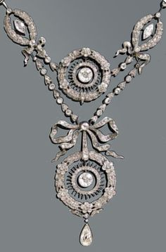 Platinum and diamond necklace, circa 1900. Designed as floral and foliate garlands, the largest garland surmounted by a bow motif, set throughout with rose-cut diamonds, and suspending a pear-shaped diamond, mounted in platinum.