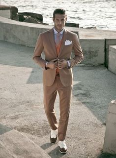 A tan suit and an orange cardigan will showcase your sartorial self. Choose a pair of white and brown leather brogues for a more relaxed feel. Shop this look on Lookastic: https://lookastic.com/men/looks/suit-cardigan-dress-shirt/20105 — Light Blue Dress Shirt — Beige Tie — White Pocket Square — Orange Cardigan — Tan Suit — White and Brown Leather Brogues
