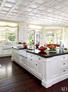 The kitchen in this Hamptons home, painted in a white, features Roman shades. See more black kitchen countertop inspiration now.