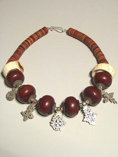 Tribal Gallery Designs | Necklace; Old African amber (dark red simulated resin, Ethiopian coin silver crosses, 2 antique Moor white conch shells and mixed heshi from the African trade period.