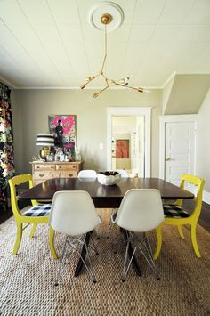 love the expressive art, the black floral curtains & the bright yellow chairs with gingham seat cushions