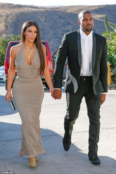 Glitz and glam: Kim Kardashian was a vision of elegance in a plunging taupe dress that cinched into her curves as she walked hand-in-hand with her husband Kanye West to a wedding in Simi Valley on Friday
