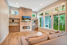 """Relax and enjoy your family in this bright and open great room boasting twelve foot ceilings! Creative Mines Stone """"wood"""" planks (Color: Monsoon). surround this Linnear gas fireplace with custom bookshelves and mantles for storage one either side. @creati"""
