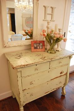 I love the way the distressed look is tied in through the dresser and the picture frame, and offset with clean letters in similar shade and beautiful flowers. Perfection.
