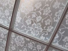 Make a frame and cover with lace....put it into the window ledge to break up the light.....bathroom window