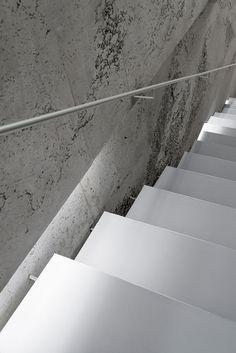 White metal staircase vs. rough concrete wall. Photo © NAARO.