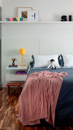 Traçado pela arquiteta, o painel da cabeceira foi produzido pela NAG Marcenaria. O abajur veio da loja Fernando Jaeger, e as obras de arte, da Mônica Filgueiras Galeria. Roupa de cama e manta do Mundo do Enxoval.