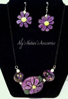 """This is a handmade Purple Daisy!! The main flower is 1 1/2"""" x 1 1/4"""" and the 2 """"cane"""" round beads are 1/2"""".  Necklace is on a black 18"""" chain with a hook clasp. This only weighs 1.2oz.  The earrings are 1 1/4"""" x 1 1/4"""" on hook earrings and only weigh .2oz for both.    $15.00 plus shipping if needed."""