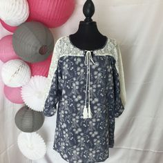 A denim look flower printed dress makes this lightweight and comfy. Flowers are huge this season!! Lace runs from sleeve to sleeve and across the shoulders adding lots of great detail. We love to pair