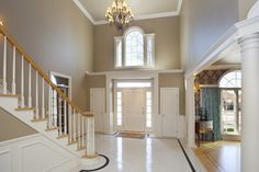 Classy large foyer with tiles flooring and high ceiling. The light gray walls ma. Classy large foyer with tiles flooring and high ceiling. The light gray walls matches the white det Foyer Design, Foyer Wall Decor, Foyer Paint Colors, Foyer Decorating, Modern Foyer, Light Grey Walls, Foyer Chandelier, Colored Ceiling, High Ceiling