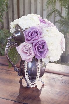 A vintage silver teapot centerpiece filled with soft purple roses, ivory hydrangeas and strands of pearls. {Danielle Ford Photography}
