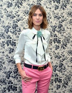 Alexa Chung in Los Angeles wearing a Gucci Cruise 2016 white silk ruffle blouse with black grosgrain neck tie and blue silk flower with a pair of pink wool trousers, black leather GG Marmont belt, black leather loafers with horsebit detail and icon blossom ring in 18kt yellow gold.