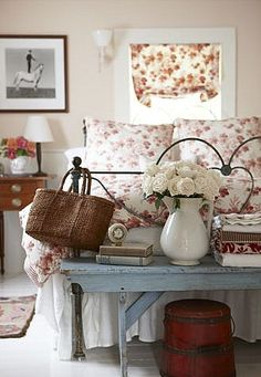 white painted wood floor, white pitcher with white flowers, pale blue bench, floral bedding and matching curtain