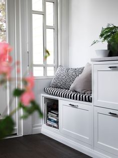 Ett vitt avskalat kök med luckan Gastro med känslaav platsbyggt. Bänkskiva i marmor och handtag med svart läder.