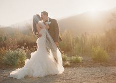 461_Designer_Bridal_Gown_Kiss - Fashionable wedding dress worn by a gorgeous bride. Photographer, Michael Costa backlit this romantic shot of the new husband and wife using natural light during sunset. The bride & bridesmaids got ready at Ojai Valley Inn & Spa. The ceremony and reception location was held at Red Tail Ranch, a private estate in Ojai, California owned by the brides family. This wedding was planned by the ever talented Joy Proctor of Joy Proctor Design based out of Santa…